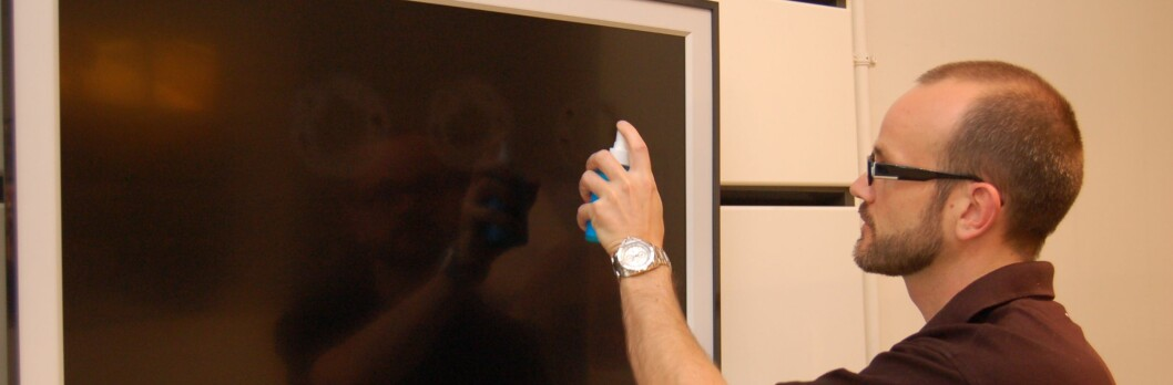 Christian Uhre demonstrerer hvordan man rengjør skjermen. Foto: Olav Eggesvik