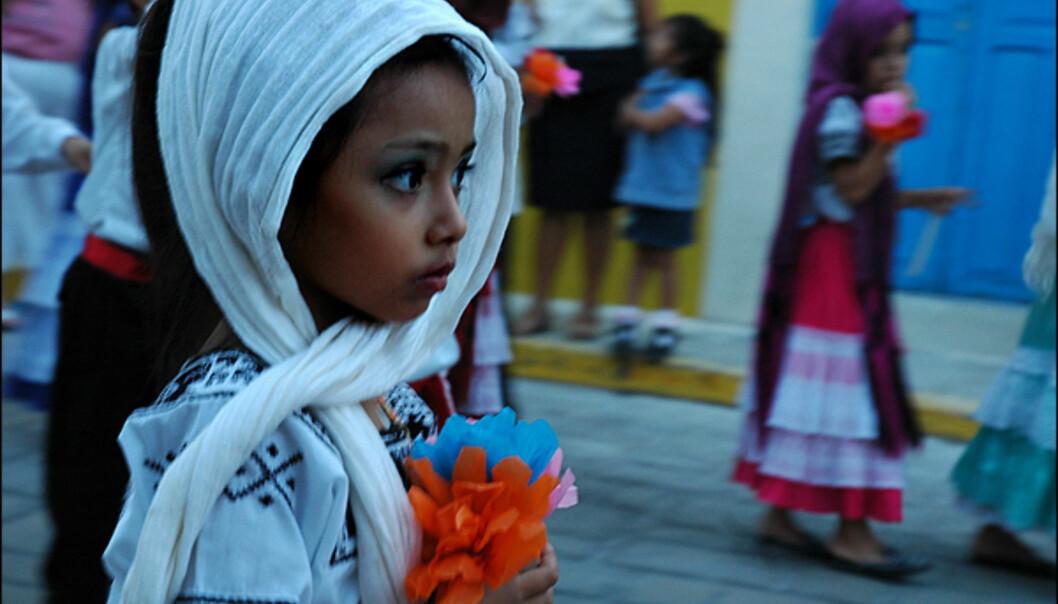 <strong><b>Over:</strong></b> En liten jente paraderer tydelig spent mot målet og arenaen, hvor folkemassene venter på forestillingen. <br /> <br /> <br /> <br /> <br /> <br /> <br /> <br /> <br /> <b>Under:</b> Fortet i Campeche er en imponerende påminnelse om den strabasiøse fortiden til byen. På 1500- og 1600-tallet var Campeche hovedhavnen i den mexicanske delen av Gulfen, og ble konstant plyndret av pirater. <br /> <br /> Det var <i>log wood</i>, et type trevirke som ga sterk rødfarge til europeernes stadig voksende motebevissthet, som ga området en enorm rikdom. I tillegg ble store laster med gull, sølv og edelstener skippet ut fra byen mot Europa. Noe som var uimotståelig for de blodtørstige røverne. På slutten av 1600-tallet måtte kanoner og borgvegger til for å stoppe rebellene.