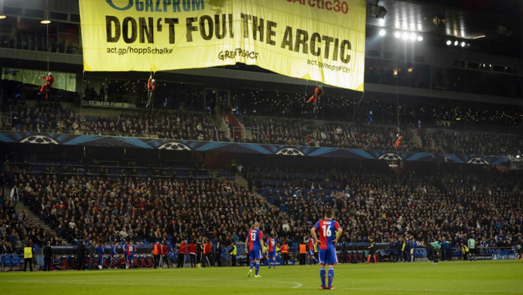 <strong>RISIKERER REAKSJON:</strong> Fire oransjekledde Greenpeace-aktivister protesterte mot russiske Gazprom i gårsdagens kamp mellom Basel og Schalke. Nå kan hjemmelaget vente en kraftig reaksjon fra UEFA. Foto: AP Photo/Keystone, Laurent Gillieron/ NTB Scanpix