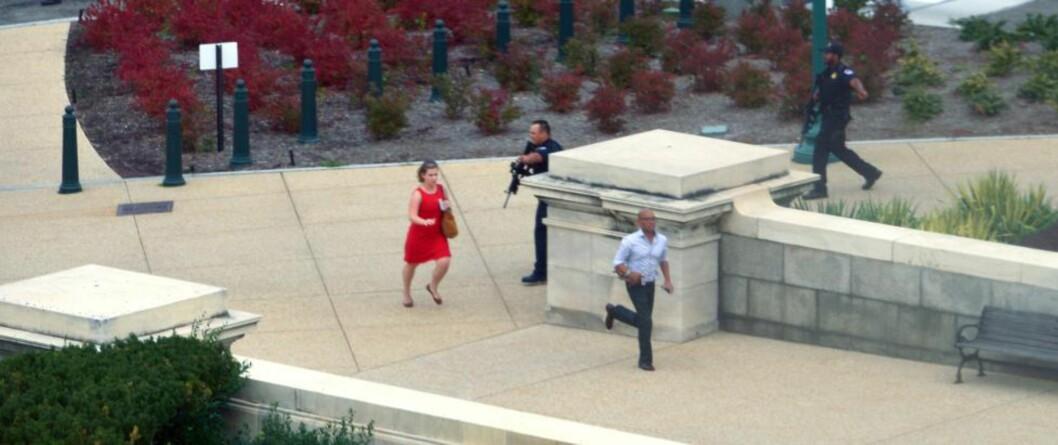 <strong>SKYTEEPISODE:</strong> Mennesker flykter fra Kongressbygningen og får bistand av væpnet politi på Capitol Hill iWashington, DC. Foto: Mandel NGAN / AFP / NTB SCANPIX