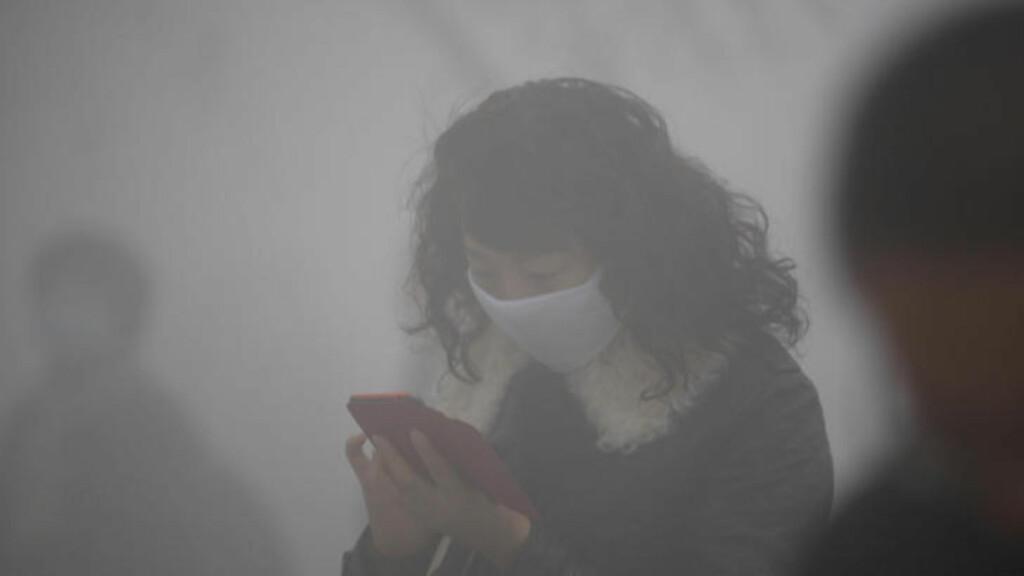 PRØVER Å LESE MOBILEN:  Denne kvinnen er ute på gata på høylys dag i Harbin tirsdag. FOTO: AFP/NTB Scanpix.