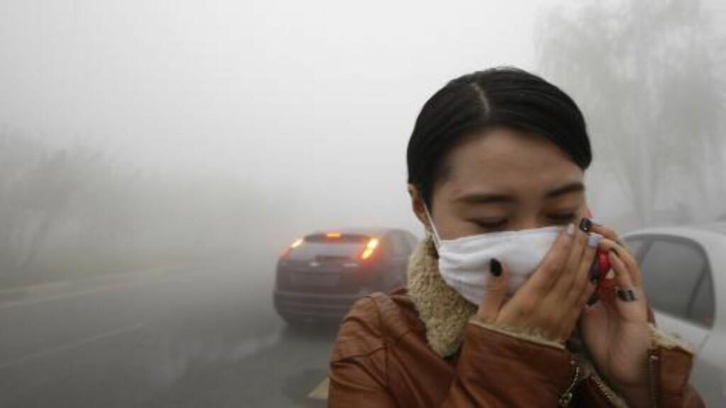 TUNGPUSTET:  Kvinne med ansiktsmasse i Harbin tirsdag. FOTO: AFP/NTB Scanpix.