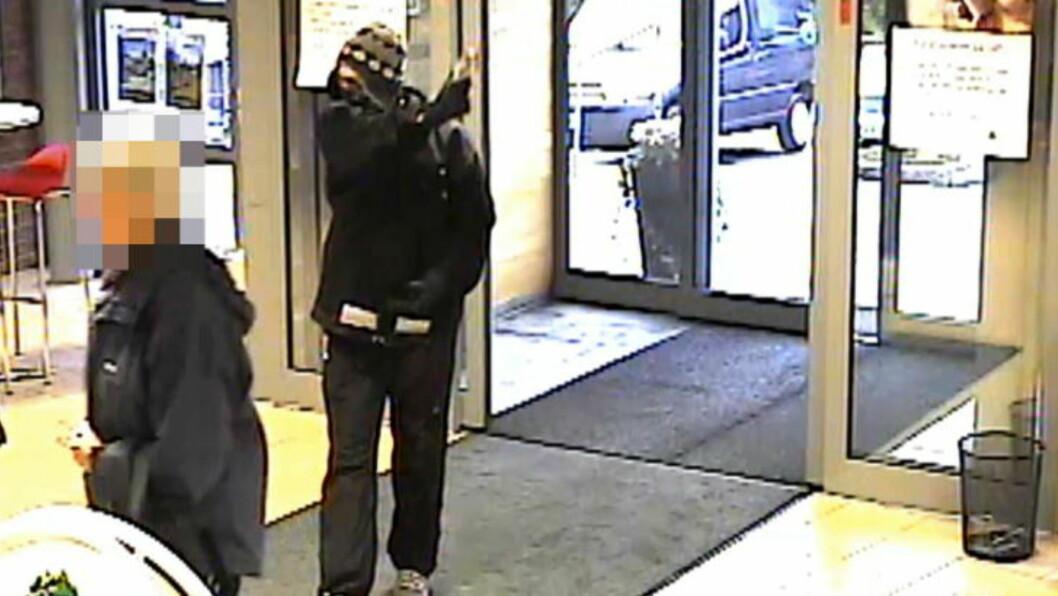 <strong>AVFYRTE SKUDD:</strong> Et overvåkningsbilde viser gjerningsmannen i det han fyrer av et skudd under ranet av Spydeberg sparebank onsdag. Foto: Politiet / NTB scanpix