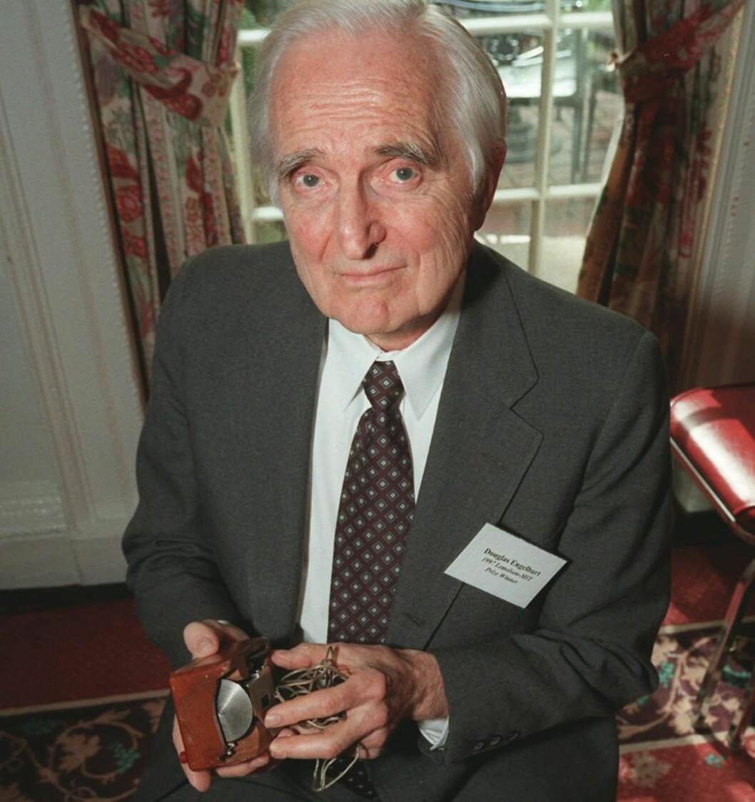<strong>DEN ORIGINALE MUSA:</strong> Doug Engelbart viser fram den første utgaven av PC-musa, som han laget på 60-tallet. Dette bildet er fra 1997. Foto: Michael Schmelling / AP.
