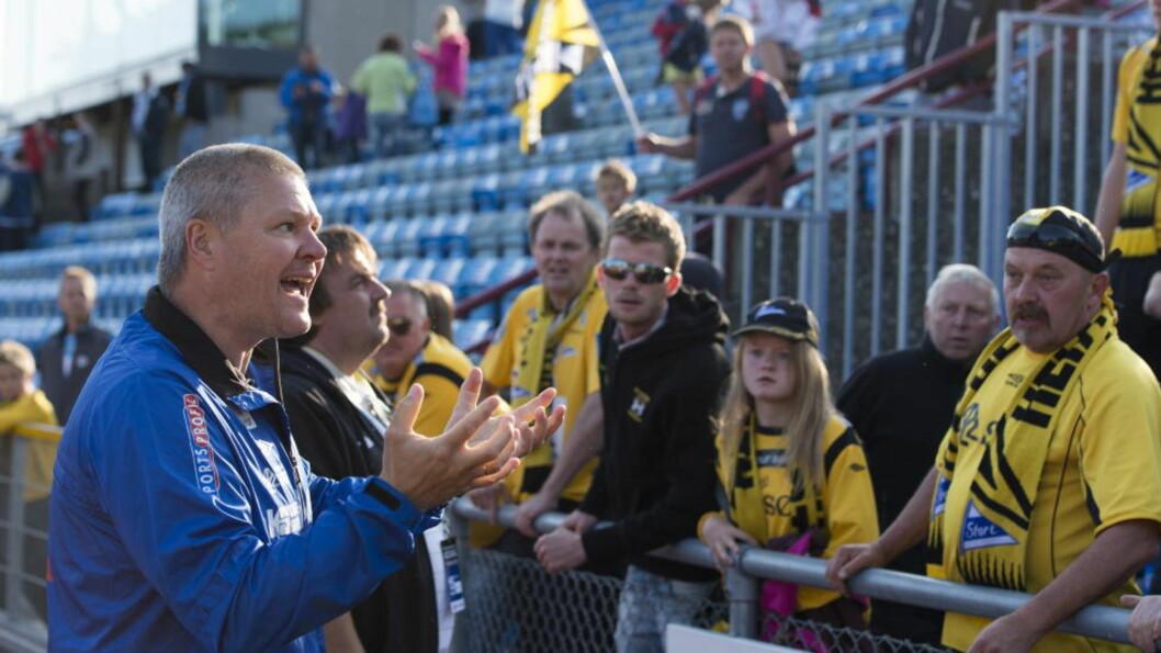 FORKLARE SEG:  Mons Ivar Mjelde måtte svare supporterne etter tapet for Sandnes Ulf. Nå ønsker draktsponsorens gründer å fjerne treneren. Foto: Kent Skibstad / NTB scanpix.