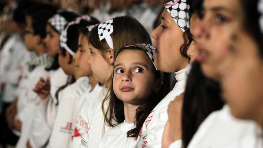 <strong>MEKTIGE SAKER:</strong> En ung palestinsk jente ser opp under en FN-kongress der koret hennes deltok. Nå har ny forskning vist hvordan korsang forener kroppenes egen rytme. Foto: Mohammed Abed / AFP / NTB Scanpix