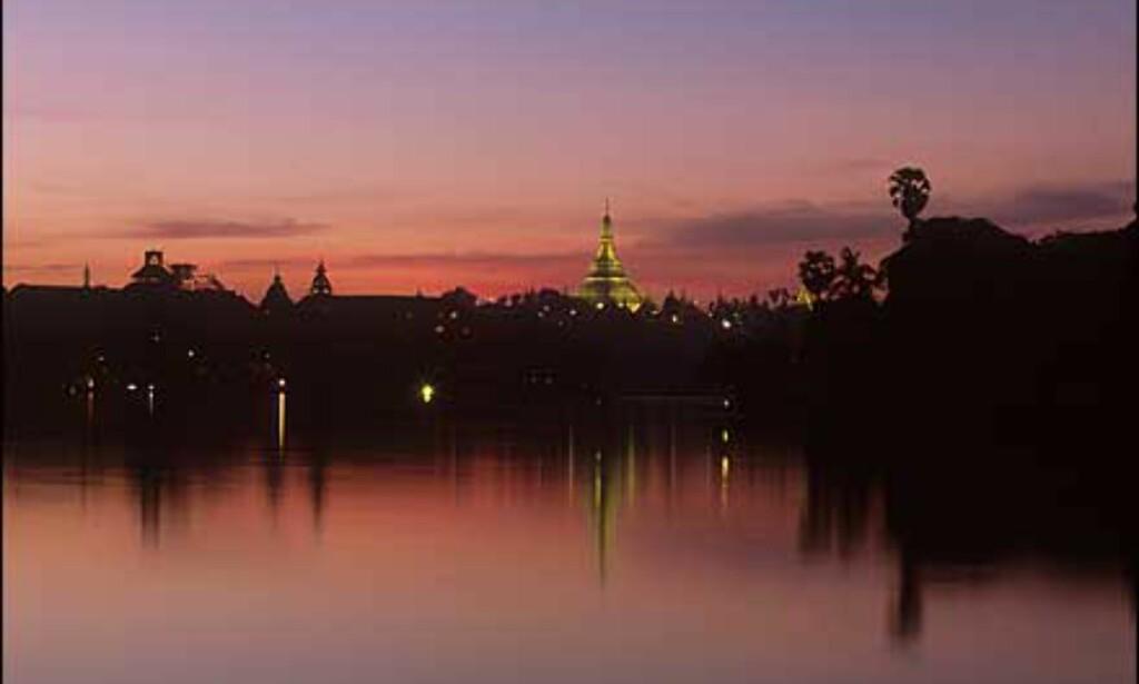 Yangon: Swedagon-templet sett fra Kandawgyi. Et av de fremste buddhisttempler i verden, og en av de viktigste severdighetene i Yangon. Kuppelen og annen dekor består blant annet av tilnærmet ni tonn gull. Pagoden er 99 meter høy.   - De gamle kolonibygningene og innsjøene rundt byen er også verdt et besøk. Yangon, eller Rangoon, er en langt mer behagelig by enn f.eks. Bangkok. Ikke glem å ta en kald øl på legendariske Strand Hotell som er et typisk britisk kolonihotell av høy standard, forteller Stenersen. Foto: Haakon F. Stenersen