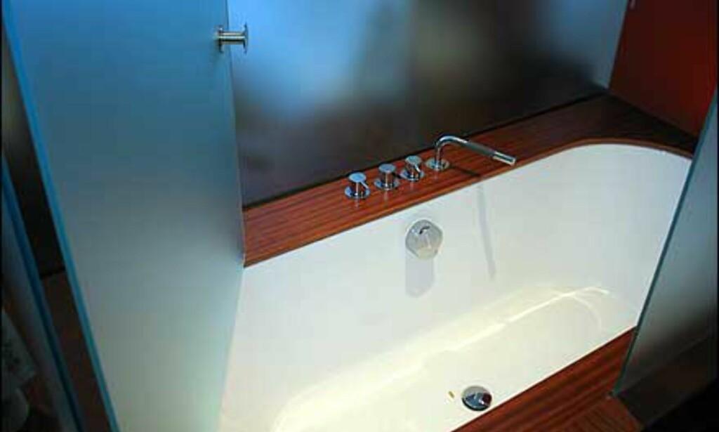 Badekar rammet inn i edeltre og matt glass.