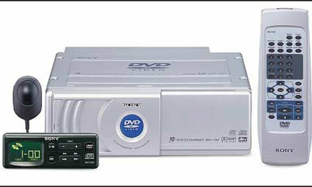 DVX 100 DVD-veksler med plass til 10 plater. Veiledende 9.800 kroner. RF-modulator, kan kobles opp mot hvilken som helst head-unit(med radio). Spiller DVD, VCD, CD, CD-R. Har bla. Optisk digital utgang (Dolby Digital & DTS) Analog audio utgang x 1 • Visuell utgang (fram & bak) • IR-mottager med fjernkontroll • Separat display • Monitor modes; Wide, 16:9, 4:3, letterbox,  4:3 Pan & Scan
