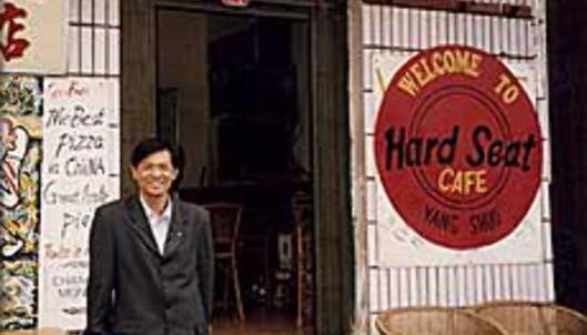Innehaveren i Vietnam viser stolt fram verdens første <i>Hard Seat Cafe</i>.<br /> <i>Bilde: Kristin Bjerkeland</i>