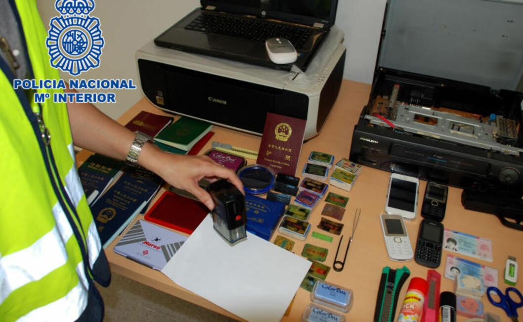 <strong>KJEMPEBESLAG:</strong> Politiet har tatt beslag et stort antall gjenstander de mener er brukt til å produsere falske pass til «klientene». Beslaget omfatter bl.a. flere PC-er, stempler og skrivere, samt ferdigproduserte pass. Foto: SPANSK POLITI / DET SPANSKE INNENRIKSDEPARTEMENTET / AFP / NTB SCANPIX
