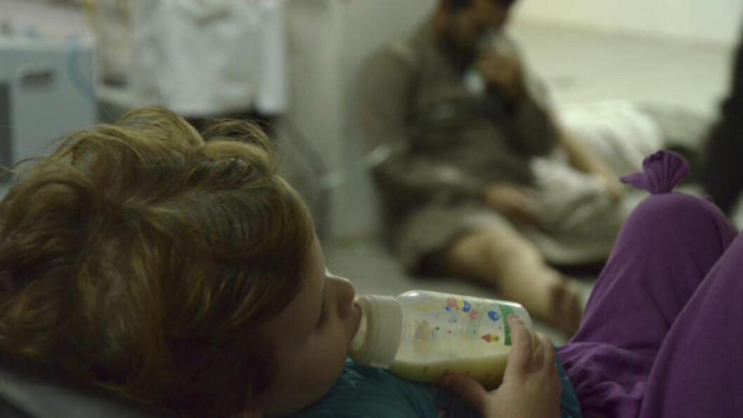 FÅR HJELP: Over ett tusen menn, barn og kvinner ble drept i syreangrepet forrige uke. En liten jente mates, mens mannen i bakgrunnen får oksygen gjennom en maske på sykehuset i Saqba utenfor Damaskus. Foto: REUTERS / Bassam Khabieh / NTB Scanpix