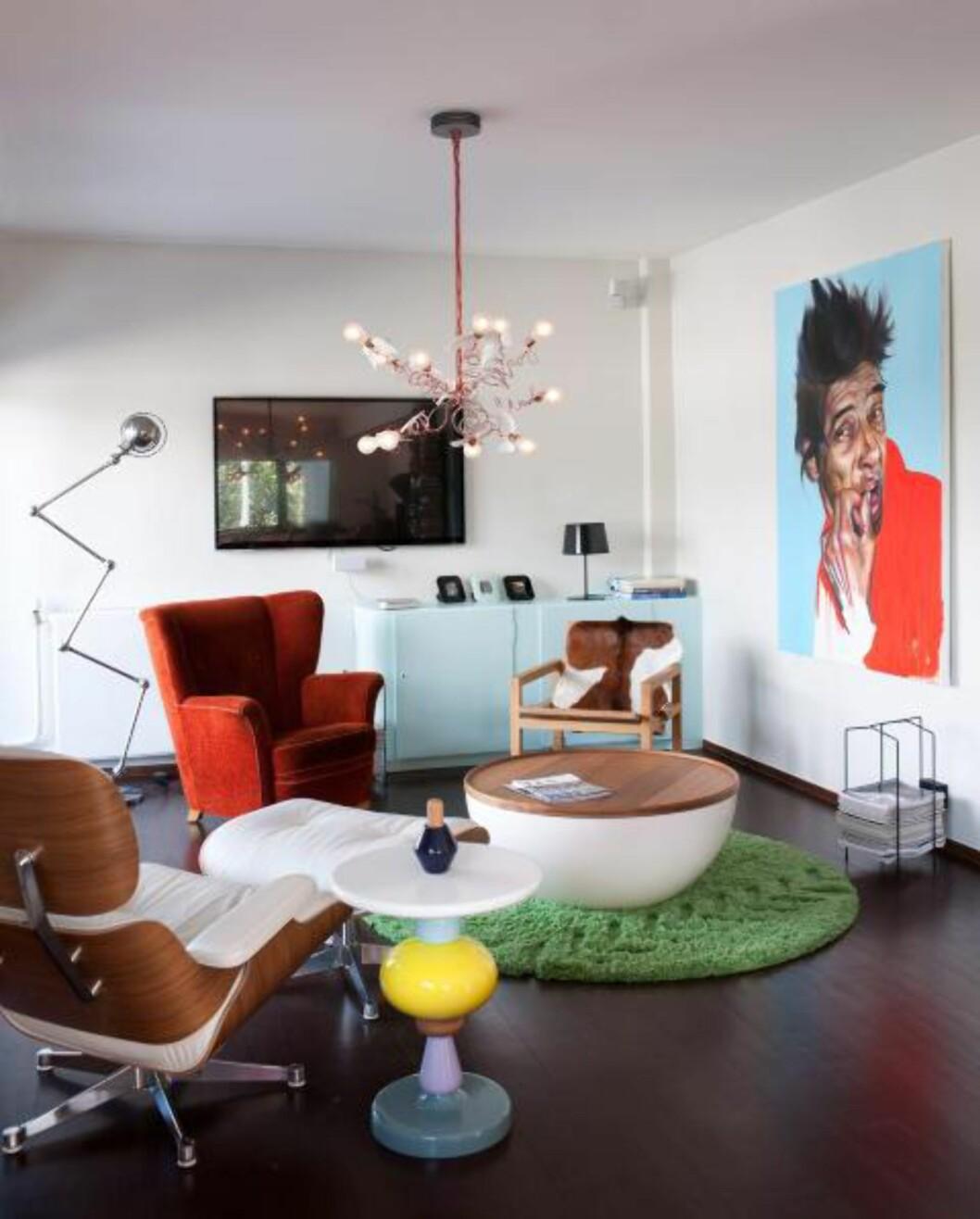 <strong>SOFALØS STUE:</strong> Stua er innredet med en uvanlig møbelmiks: Eames Lounge Chair fra Vitra, Shuffle sidebord fra Andtradition, bord med oppbevaringsplass fra Bolia, en gammel ørelappstol og en enkel hvilestol fra R.O.O.M. kledd med kuskinn fra Ikea. Gulvteppet er fra Permafrost, taklampa fra Ingo Maurer. Bildet er malt av Kristoffer Evang. Flatskjermen er nesten borte i vrimmelen. © Foto: Espen Grønli