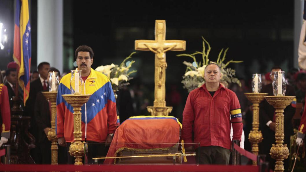 <strong>MAKTSKIFTE:</strong> Visepresident Nicolas Maduro (til venstre) har overtatt makta som midlertidig president i Vebnezuela, men ifølge grunnloven er det presidenten i parlamentet, Diosdado Cabello (til høyre), som skulle ha overtatt nå og utskrevet nyvalg av president. Her vokter de kista med den døde. Bildet er utgitt av presidentpalasset Miraflores. Foto: REUTERS / Scanpix / Palacio Miraflores
