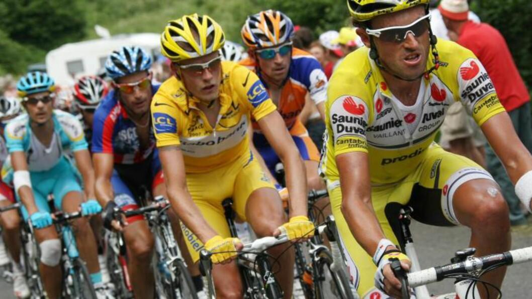 <strong>Tidligere lagkamerater:</strong> Michael Rasmussen (i gult) og Denis Menchov (bak, i oransje og blått). Foto: AFP PHOTO / FRANCK FIFE
