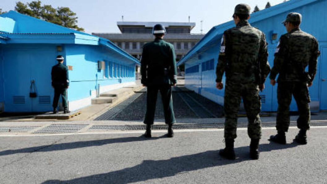 <strong>SPENT:</strong>  Grensa går midt gjennom de blå bygningene. De sørkoreanske vaktene står halvt skjult bak hjørnene, for å ha kortere vei til dekning om noe skulle skje. Foto: Cho Seong Joon/Dagbladet
