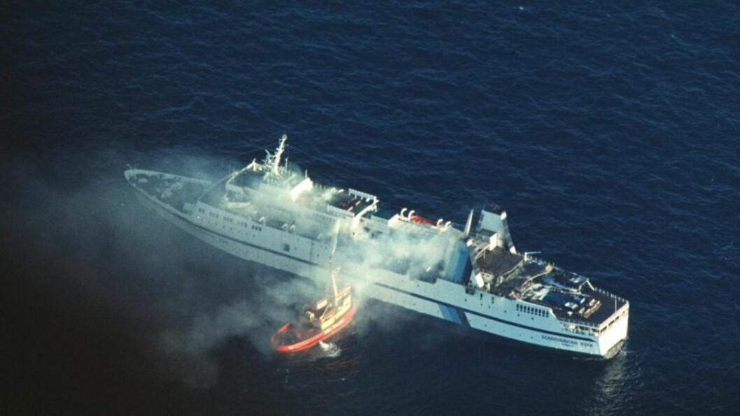 """<strong>MANGE DØDE:</strong> I 1990 brant det om bord passasjerfergen """"Scandinavian Star"""" i Skagerak mellom  Oslo og Fredrikshavn. 159 mennesker omkom i brannen. Flyfoto av skipet  i brann . Foto: Per Løchen, SCANPIX"""