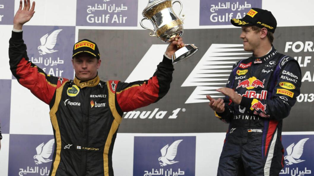 <strong>VANT:</strong> Red Bull-sjåfør Sebastian Vettel (t.h.) klapper idet Lotus-sjåfør Kimi Raikkonen mottar sin pokal for andreplassen i Bahrain Grand Prix. Selv vant Vettel løpet. Foto: AP Photo / Hassan Ammar / NTB Scanpix