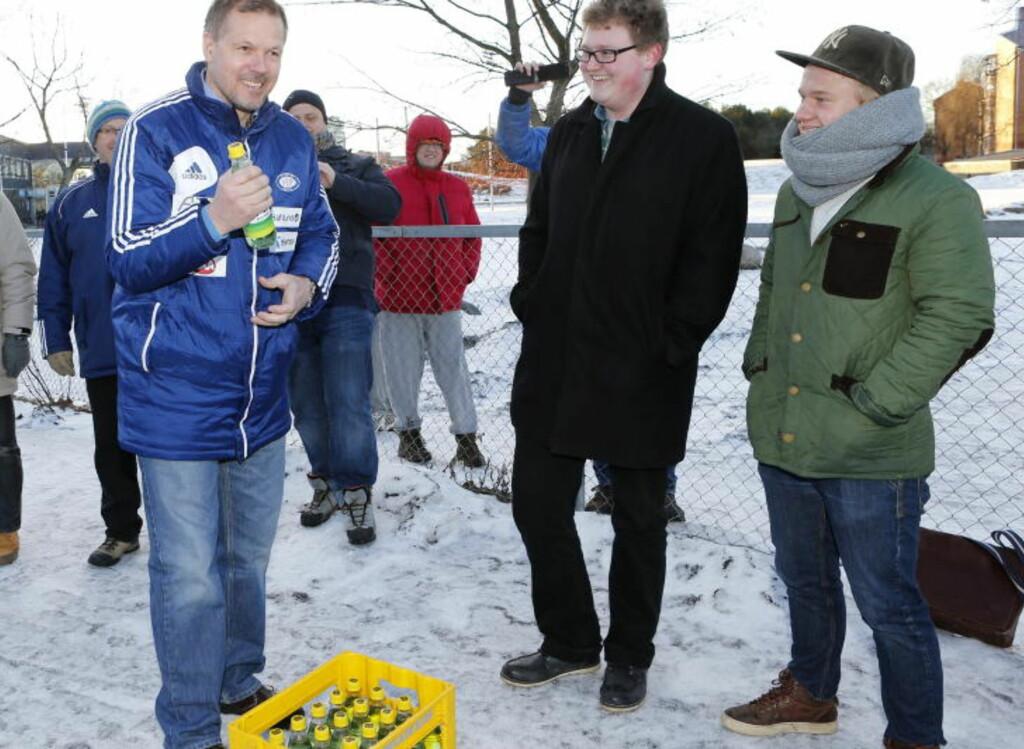 VARM VELKOMST I KULDA: Kjetil Rekdal fikk en kasse pærebrus av VIF-supporterene Magnus Håkonsen og Sondre Solvang Midtskogen før sin første trening med Vålerenga. Foto: CORNELIUS POPPE / NTB SCANPIX