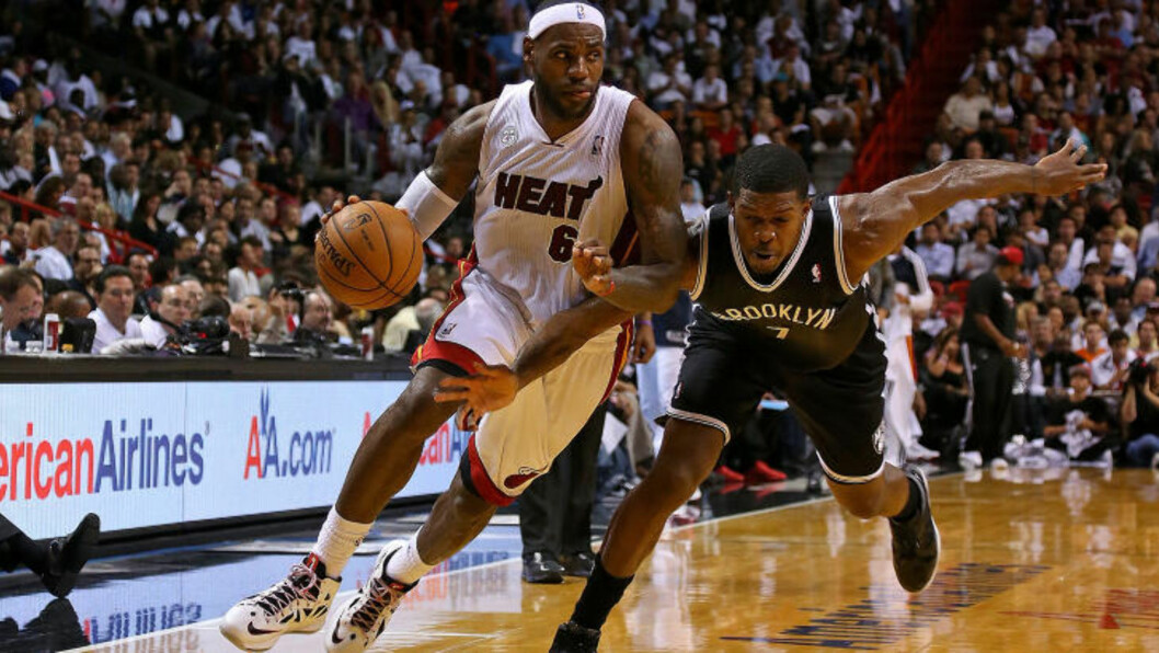 <strong>UKAS ANDRE STORSEIER:</strong> LeBron James passerer Joe Johnson. Mandag vant Miami Heat med 25 poeng mot Phoenix, i natt ble det 30 poengs margin mot Brooklyn.Foto: MIKE EHRMANN / GETTY IMAGES / AFP / NTB SCANPIX