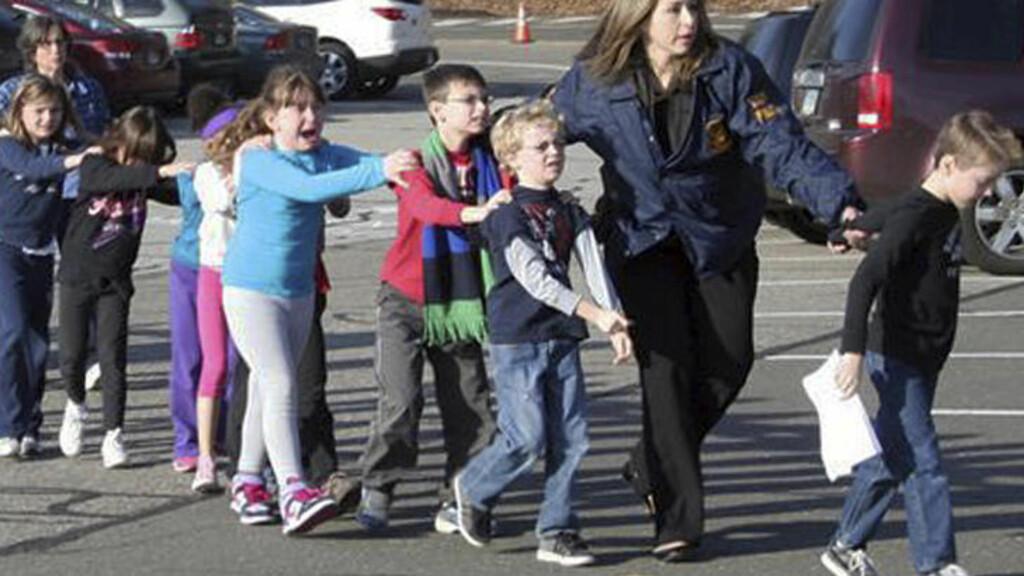 REDDE: Her blir tydelig livredde barn eskortert fra en barneskole i Connecticut. Foto:AP Photo/Newtown Bee, Shannon Hicks/NTB Scanpix