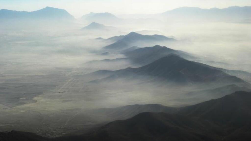 VAKKERT FRA AVSTAND: Et teppe av tåke dekker deler av fjellene nord for Afghanistans hovedstad Kabul.  Foto: NTB Scanpix /AFP PHOTO / ROBERTO SCHMIDT