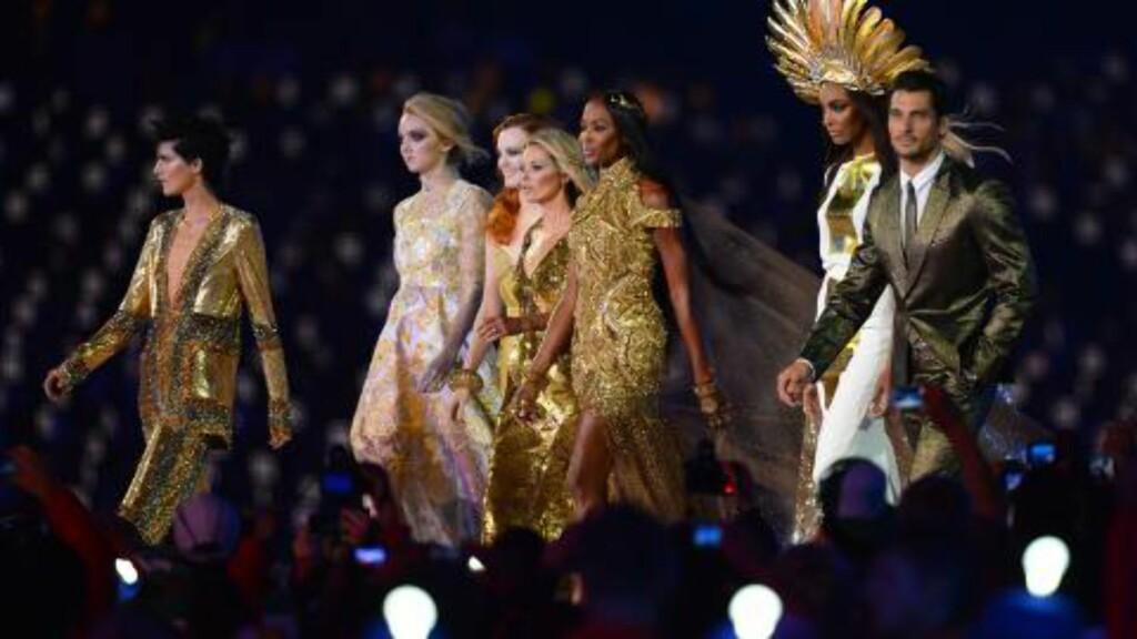 MODELLPARADE: De britiske modellene Stella Tennant, Lily Cole, Karen Elson, Kate Moss, Naomi Campbell, Jourdon Dunn og David Gandy hedret britisk mote.   Foto: AFP Photo / JEWEL SAMAD / NTB Scanpix