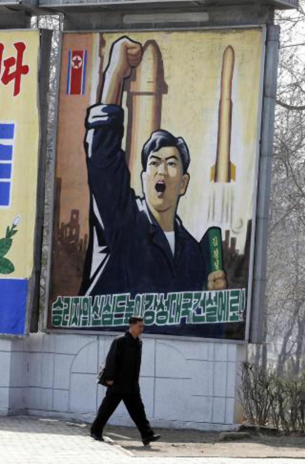 <strong>PROPAGANDA:</strong> En nordkoreaner går forbi en propagandaplakat i Pyongyang i Nord-Korea. Foto: AP Photo/Ng Han Guan/NTBScanpix
