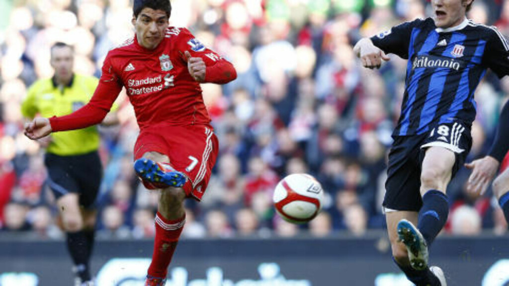 Liverpool's Luis Suarez (L) scores against Stoke City during their English FA Cup quarter-final soccer match at Anfield in Liverpool, northern England March 18, 2012.      REUTERS/Phil Noble (BRITAIN  - Tags: SPORT SOCCER)