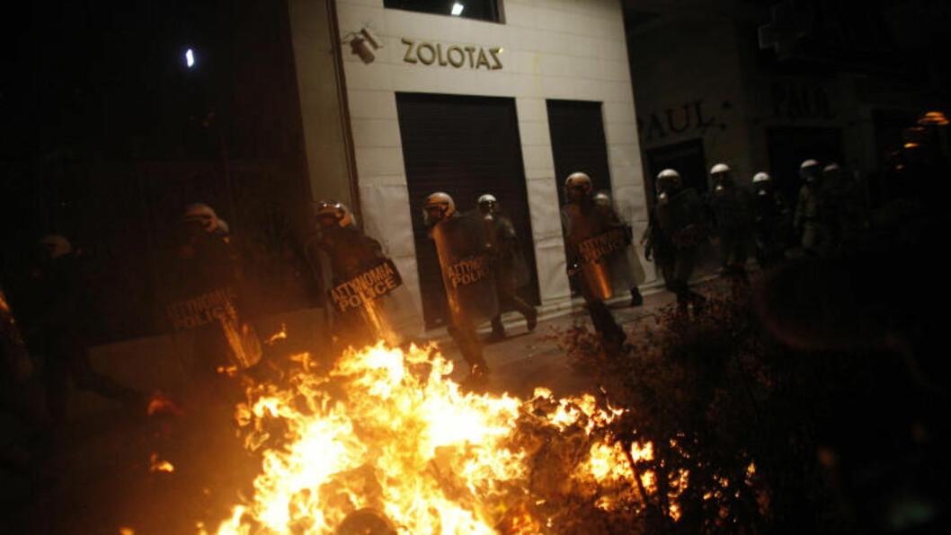 <strong>POLITI:</strong> Opprørspoliti løper forbi en brennende barikade under sammenstøtene i dag. Foto: Scanpix/AP Photo/Kostas Tsironis