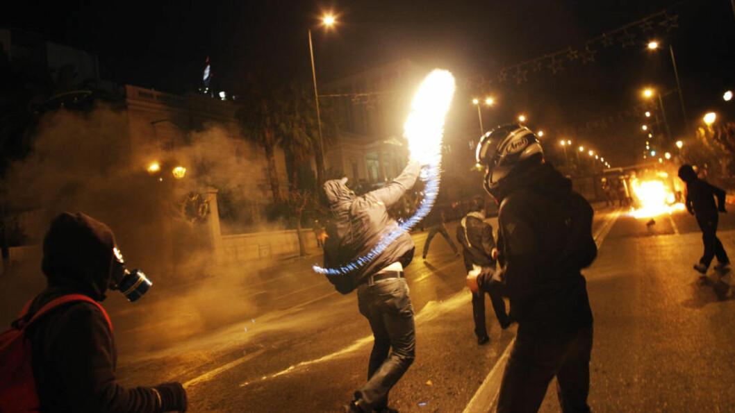 <strong>SAMMENSTØT:</strong> En demonstrant kaster en brannbombe mot opprørspolitiet utenfor parlamentet i Aten. Foto: SCANPIX/AFP PHOTO/ Angelos Tzortzinis