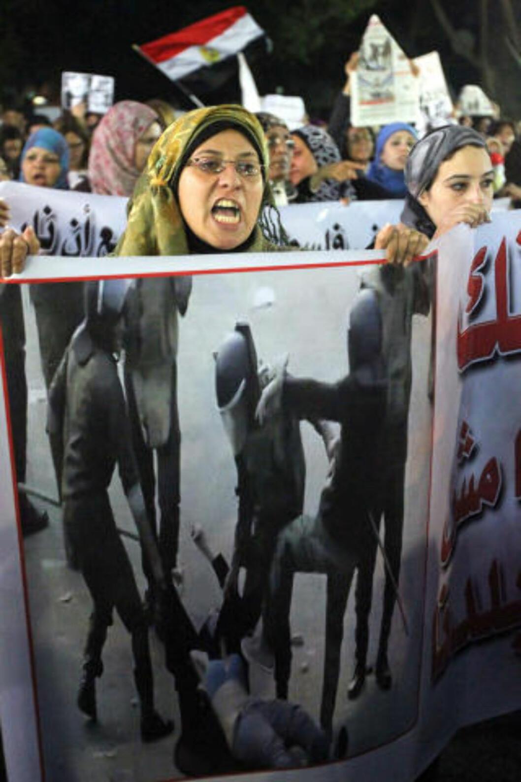 <strong>VIL HA EN SLUTT PÅ VOLDEN:</strong> 20. desember strømmet egyptiske kvinner ut i gatene i Kairo for å vise avsky mot vold mot kvinner. Her holder en kvinne opp bilder hvor en kvinnelig demonstrant bankes opp av soldater. Foto: AFP PHOTO/KHALED DESOUKI