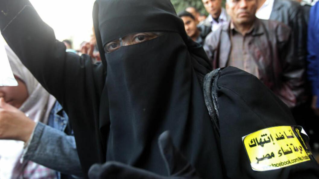 <strong>VIL IKKE KRENKES:</strong> En egyptisk kvinne i burka demonstrer i Kairo 20. desember. På armen hennes står det Jeg er imot krenkelse av egyptiske kvinners ære. Foto: AFP PHOTO/KHALED DESOUKI