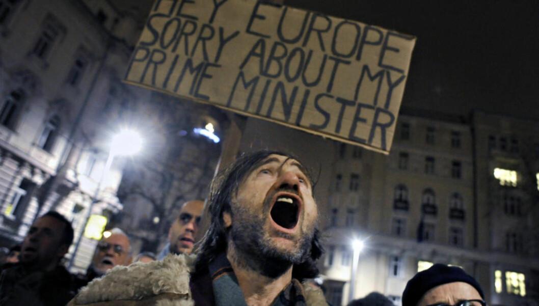 MØTER KRITIKK: Demonstranter er kritiske til statsminister Viktor Orbán. «Ungarns nye grunnlov har ført til internasjonal oppmerksomhet. USAs regjering har sendt gjentatte kritiske signaler», skriver kronikkforfatteren. Foto: Béla Szandelszky/AP/Scanpix