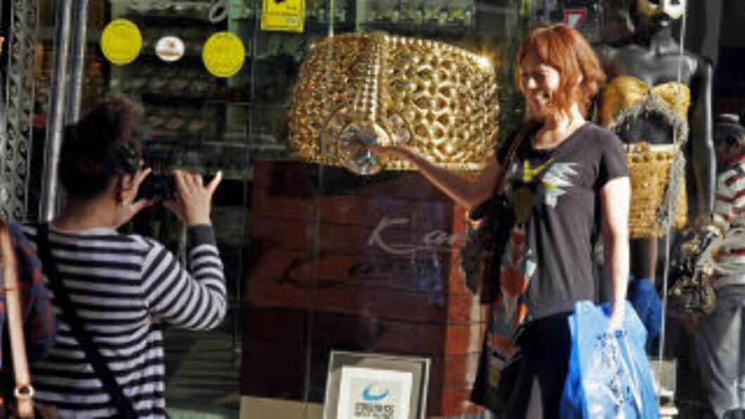 <strong>POPULÆRT MOTIV:</strong> Verdens største gullring trekker kunder i bøtter og spann, og mange ønsker å bli fotografert sammen med monsteret. Foto: EIVIND PEDERSEN