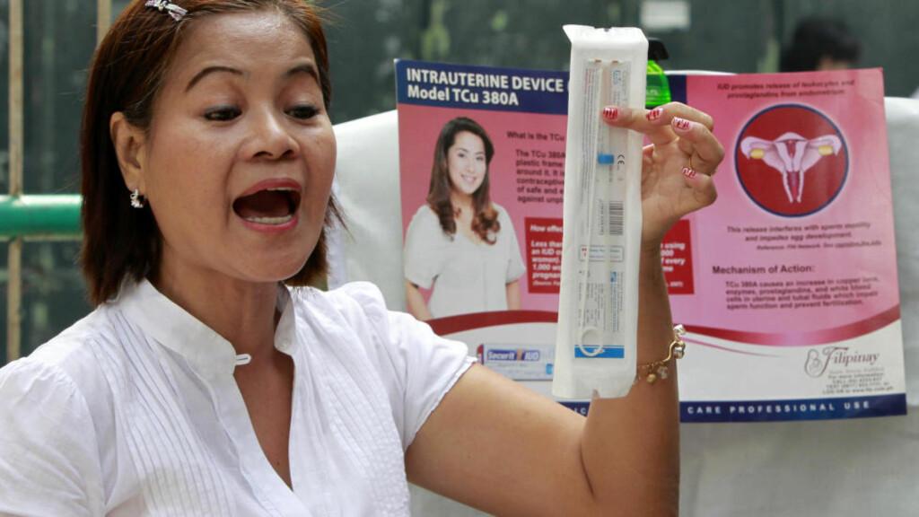 VANLIG PREVENSJONSMIDDEL: En ny studie viser at spiral minsker risikoen for livmorhalskreft, en vanlig krefttype blant kvinner. Fra før er det kjent at den også beskytter mot kreft i livmoren. Spiral regnes som et effektivt prevensjonsmiddel, og her viser en helsearbeider fram en type spiral i Manila på Filippinene. Foto: Reuters/Scanpix