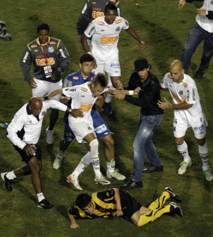 I TRØBBEL: Neymar har blendende ferdigheter, men havner samtidig stadig i problemer. Her er han involvert i masseslagsmålet etter at Santos slo Penarol i Copa Libertadores-finalen i natt. Men det skal det også sies at så og si alle spillerne på begge lag var. Foto: Silvia Izquierdo, AP/Scanpix
