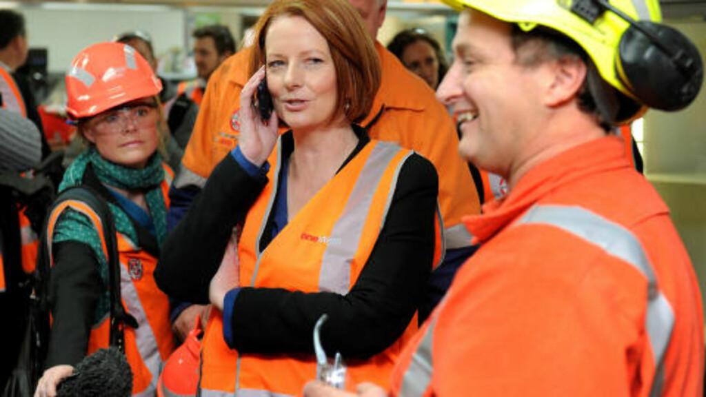 PÅ TURNE: Julia Gillard reiser nå landet rundt i håp om å få støtte til CO2-avgiftsplanen sin fra et i utganspunktet veldig skeptisk folk. Her snakker hun med kona til en arbeider på telefon ved OneSteel's mill i en av Melbournes forstader. Foto: AFP PHOTO/William WEST