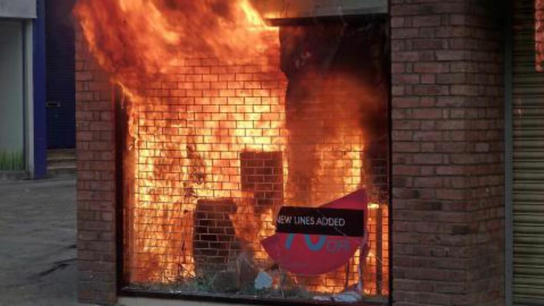 <strong>I BRANN:</strong> En butikk i Manchester er satt fyr på av pøbler. Foto: EPA/Dave Thompson/Scanpix
