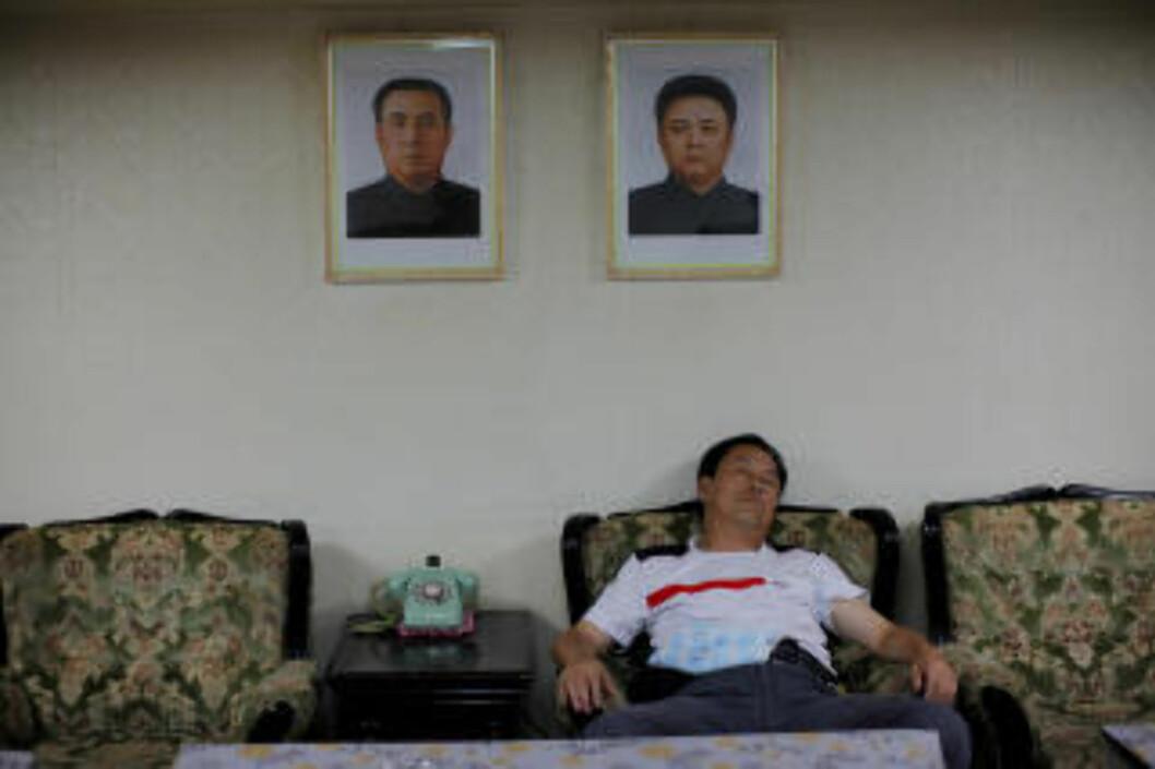 SLAPPER AV: Et medlem av den kinesiske turistdelegasjonen sover under bildene av Nord-Koreas leder Kim Jong-II og hans avdøde far Kim II-Sung.  Foto: CARLOS BARRIA/REUTERS/SCANPIX