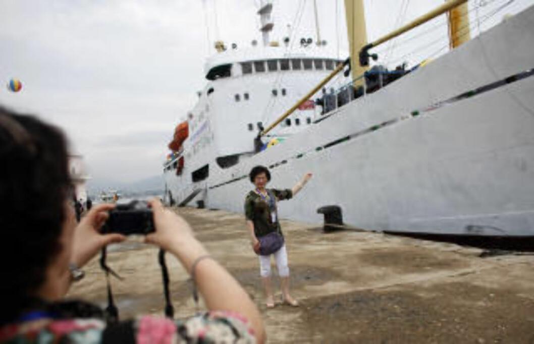 SKAL LOKKE TURISTER: Gjester tar bilder av skipet Mangyongbong før ombordstigning. Nord-Korea har vært åpent for vestlige turister siden 1987, men besøkene er både strengt kontrollert og nøye overvåket. Enkelte områder har likevel blitt åpnet gradvis mer og mer, så turgrupper kan se landet på egenhånd. Foto: CARLOS BARRIA/REUTERS/SCANPIX