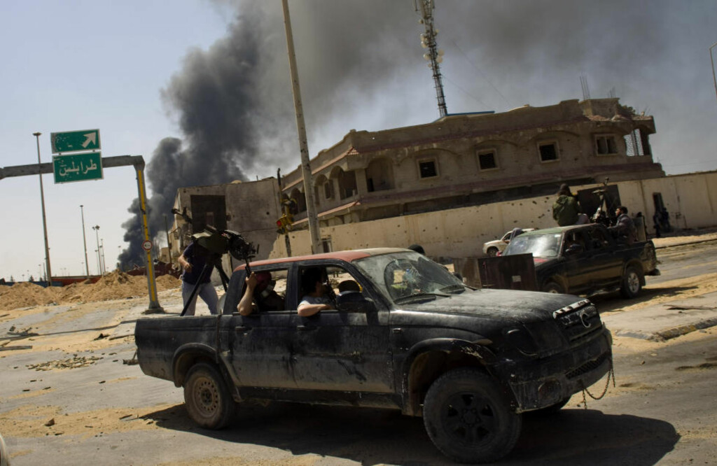 "Rebel fighters make their way to the frontline in Misrata, Libya, Friday, April 29, 2011. The traffic signal at back reads ""Tripoli"". (AP Photo/Bernat Armangue)"
