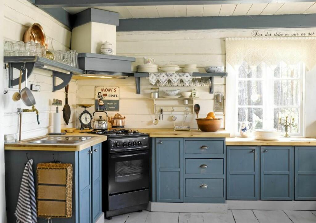 SELVLAGET: Det nydelige, blå kjøkkenet er det Arne som har bygget. Den smarte hjørneløsningen med ovnen var hytteeiernes egen idé. Det gamle skiltet har Hilde kjøpt i en interiørforretning i Arendal. Kobberkjelen tilhørte Arnes tippoldeforeldre, og stammer fra tidlig 1800-tall. FOTO: Per Erik Jæger
