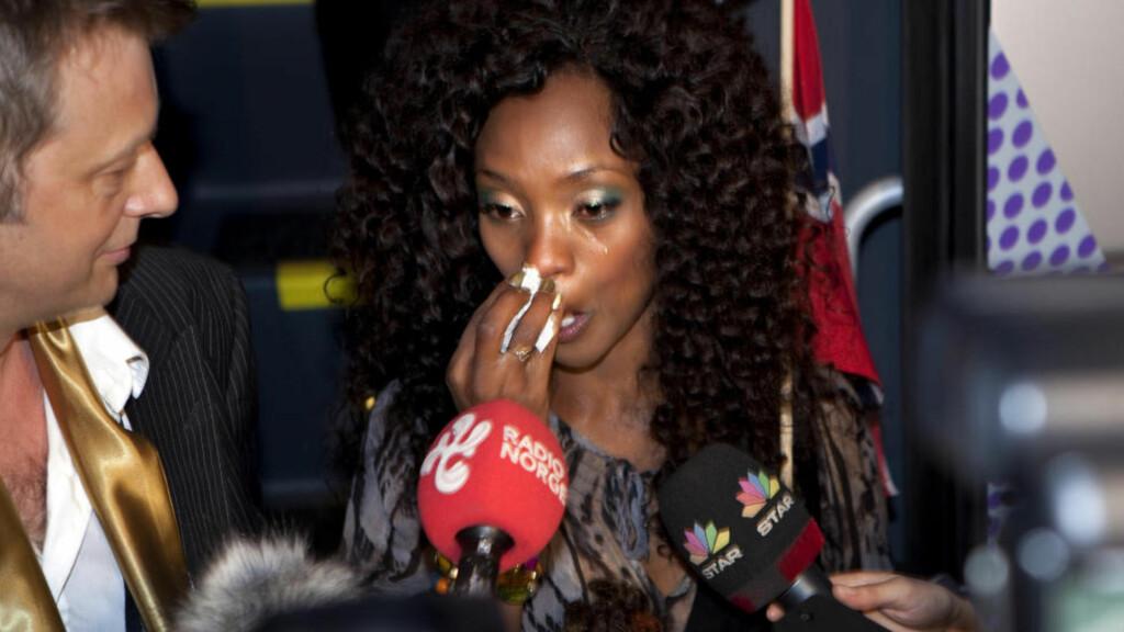 TYDELIG SKUFFET: Stella Mwangi tok til tårene da hun møtte pressen etter Eurosong-semifinalen i Tyskland i går kveld. Sjefen i plateselskapet hennes Emi, Bjørn Rogstad, depper imidlertid ikke. Nå må vi bare få henne hjem. Hun har ikke tid til å være i Tyskland, sier han. Foto: Anders Grønneberg