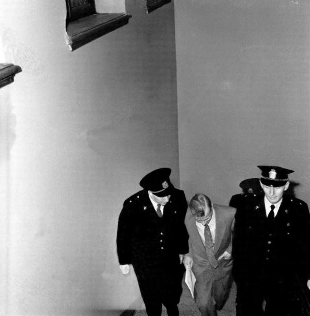 TRODDE IKKE PÅ HANS ALIBI ELLER FORKLARING: Fredrik Fasting Torgersen føres her inn i rettsalen av tre politimenn i Oslo Tinghus sommeren 1958.