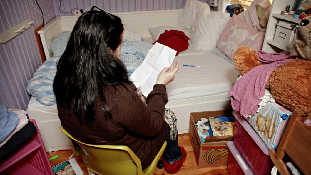 SÅR HILSEN: Her sitter kvinnen som har tatt seg av Maria Amalies foreldre mens de har levd i skjul et sted i Norge siden 2003. I hånda holder hun et brev Marias mor skrev til sin datter fredag kveld. Bildet er tatt foran senga som foreldrene sov i natt til fredag. Tannbørsten og en bok om Jesus ligger igjen... Foto: Lars Eivind Bones / Dagbladet