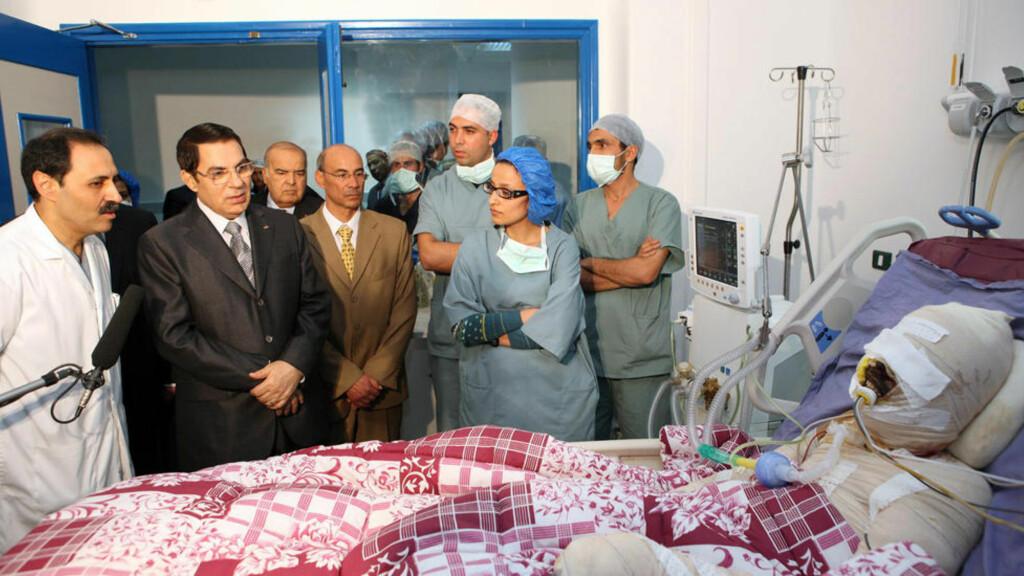 SATTE FYR PÅ SEG SELV - STYRTET PRESIDENTEN: Mange mener at den tunisiske revolusjonen startet da grønnsakshandleren Mohamed Bouaziz (26) satte fyr på seg selv 17 desember i fjor. Her besøker den tunisiske presidenten Bouaziz på sykehuset 28 desember. Fredag rømte president Zine Al-Abidine Ben landet. Bouaziz har blitt en folkehelt. Foto: SCANPIX/AP
