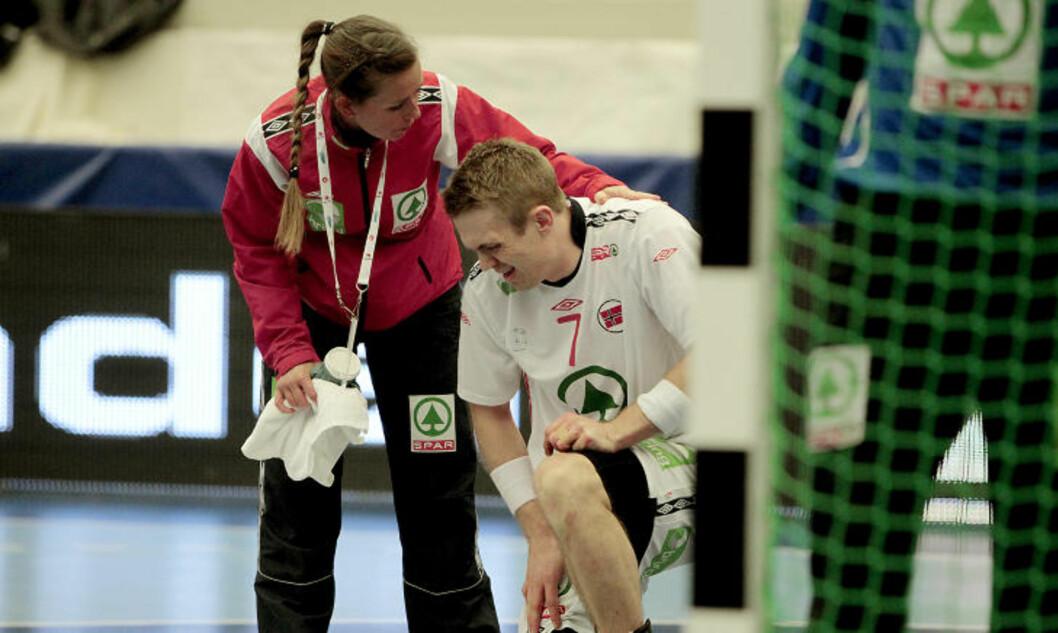 <strong>FÅR SEG NOEN SMELLER:</strong> Selv om du oftere pådrar deg smeller som bakspiller, får også Lars Erik Bjørnsen hard medfart i VM. Her får han hjelp til å komme seg på beina av fysioterapeut Maria Leitao.