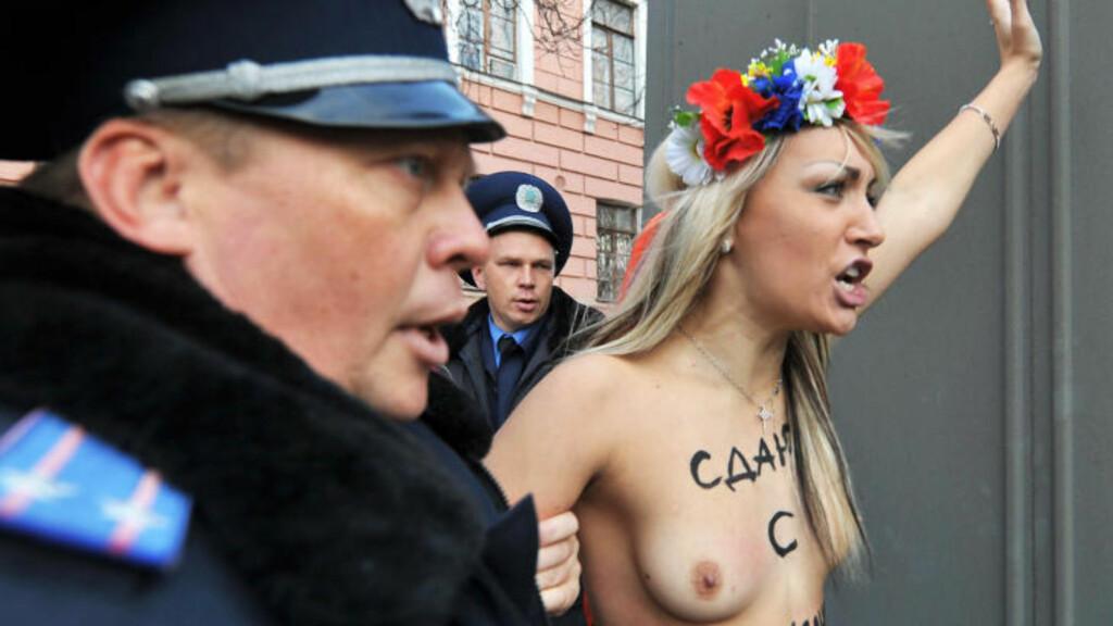DEMONSTRERTE MOT PUTIN: Politimenn pågriper en aktivist fra Femen etter at de frivillig kom til en politistasjon i Kiev i protest mot Russlands statsminister Vladimir Putins besøk Ukraina 27. oktober. Foto: AFP Photo/Sergei Seupinsky/Scanpix