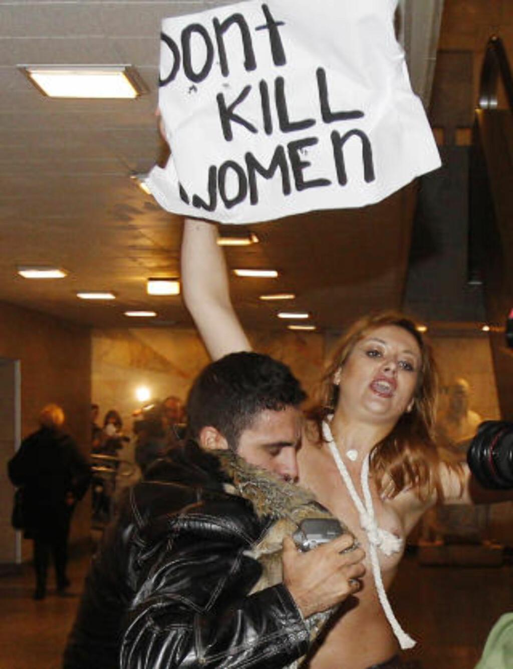 IRAN-DEMONSTRASJON: En iransk sikkerhetsvakt prøver å skjule en avkledd aktivist ved en iransk kulturbegvienhet i Kiev. Foto: Reuters/Gleb Garanich/Scanpix